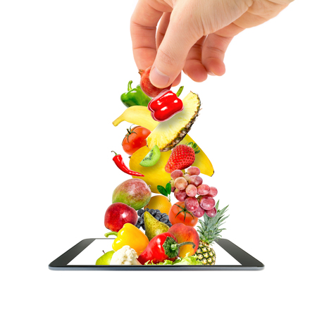 A mans hand putting a pile of fresh vegetables and fruits flying into a modern gadget, a mobile phone, isolated on a white background. Online Shopping idea.
