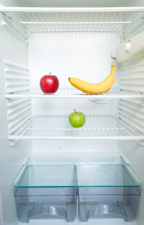 Bright fresh red and green apples and banana on shelf of open empty refrigerator. Weight loss diet concept. 版權商用圖片