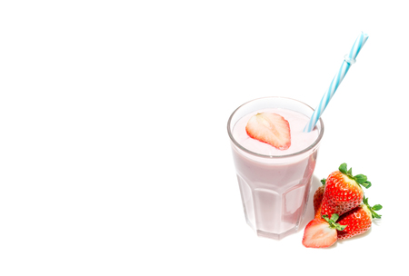 Strawberries next to a glass of strawberry yogurt milkshake close-up isolated on a white background with free space for text.