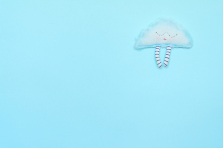 Funny cloud on blue paper background. Weather photo
