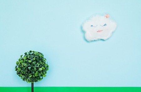 A funny cloud on a blue paper background and a toy tree with green leaves. Photos on the theme of sunny summer weather