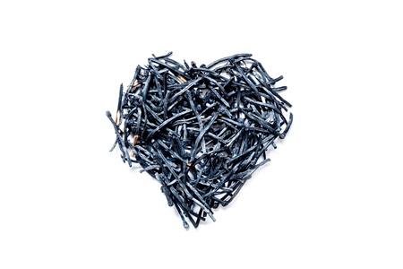 Heart symbol made of burned-down matches close-up, isolated on a white background. The concept of the complexity of love relationships, unhappy love.