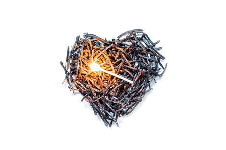 Heart symbol made of burned-down matches close-up with a burning match in the center, isolated on a white background. The concept of the complexity of love relationships, unhappy love.