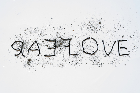 The words love and hate close-up, lined mirror of burnt down matches with ashes around on a white background. The concept of the complexity of love relationships, unhappy love. Reklamní fotografie