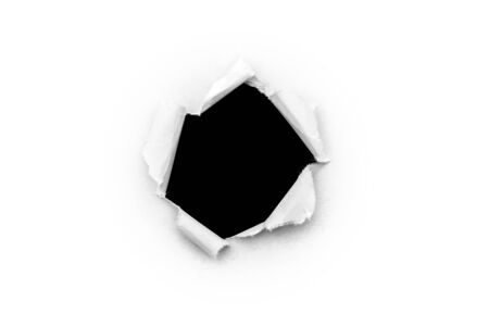 A round hole in white paper with torn edges isolated on a white background with a black isolated background inside. Фото со стока