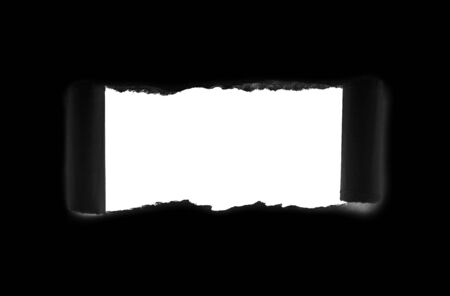 Hole in black paper with torn edges isolated with a white isolated background inside.