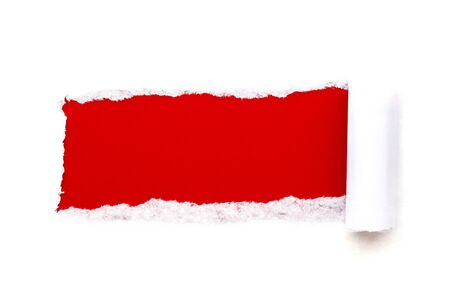 A hole in white paper with torn edges isolated on a white background with a bright red color paper background inside. Good paper texture.