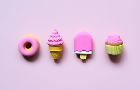 Different toy sweets in miniature with shadows close-up on a soft pink color background.
