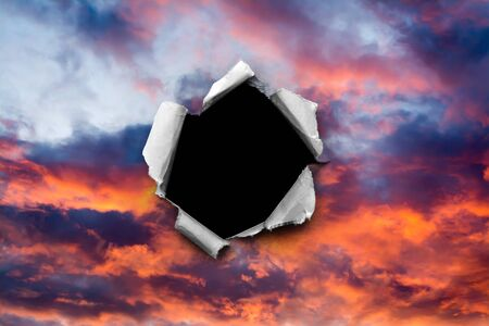 A hole in the sunset sky with torn edges, as on paper, with an isolated black space background in the center. The concept of global climate change on Earth, global warming, a hole in space and time. Stockfoto