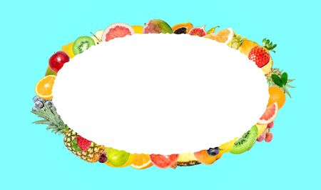 Creative photo of many different exotic tropical bright fruits on a blue background and an isolated white oval with beautiful jagged edges in the center for text. Bright summer fruit pattern.