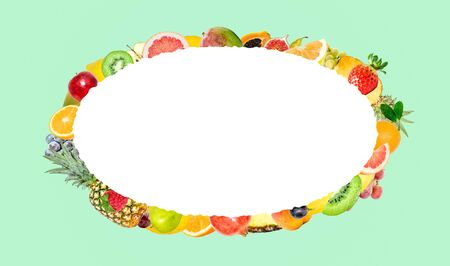 Creative photo of many different exotic tropical bright fruits on a soft green mint color background and an isolated white oval with beautiful jagged edges in the center for text. Bright summer fruit pattern.