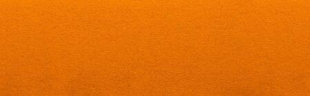 Good quality porous orange color cardboard paper texture close-up.
