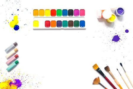 Set of colorful paints with brushes, gouache, watercolor with blots of paint on the paper and copy space in the center for text isolated on a white background. Top view. Vibrant bright color view.