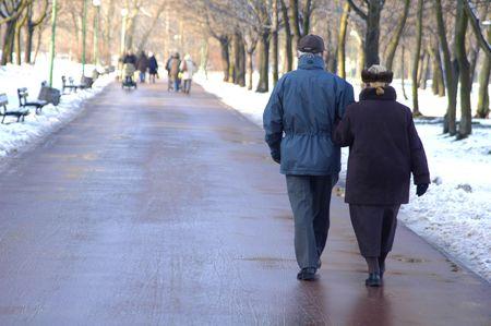 Un par de personas de la tercera edad caminando en el parque  Foto de archivo