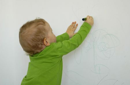 Little child drawing on the wall, conceptual issues photo