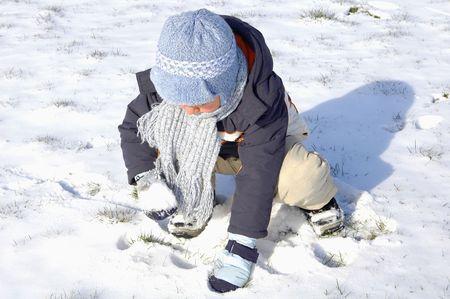 flue season: Ni�o peque�o jugando en la nieve en los d�as soleados de invierno