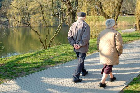 senioren wandelen: Een paar senioren wandelen in het park, metaforen