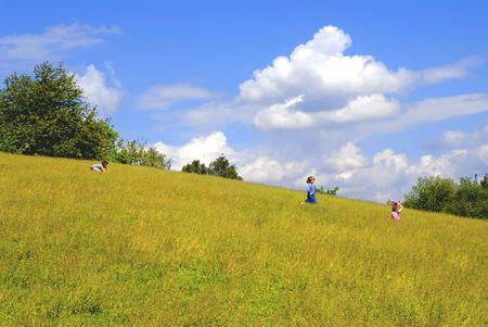 Niños jugando en la pradera, la infancia, la diversión, la temporada, la naturaleza, el ocio, cuestiones de alergia, el concepto Foto de archivo - 927500