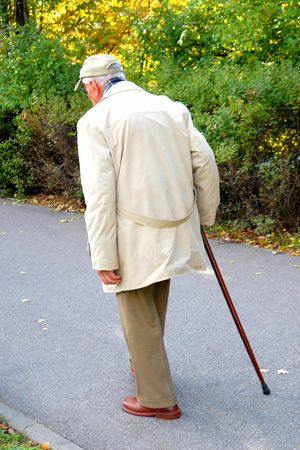 guy with walking stick: Senior walking in the park Stock Photo