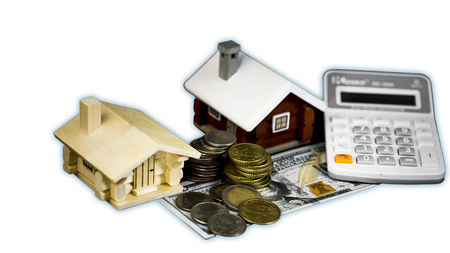 Mortgage loan and real estate tax macro financial Concept, Scandinavian house model and pile of coins money on brown wooden frame, with copy space in middle of the frame.