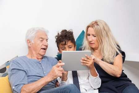 Authentic moment when boy with her grandmother and his grandfather play with a digital tablet on sofa. Smiling family with tablet at home.