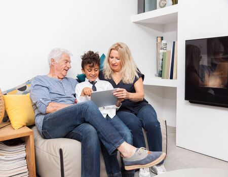 Authentic moment when boy with her grandmother and his grandfather play with a digital tablet on sofa in living room. Smiling family with tablet at home. 写真素材