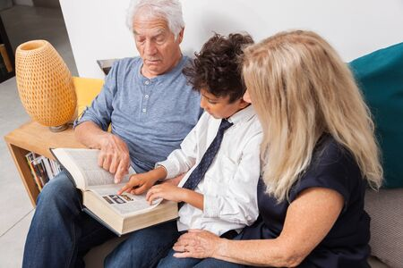 Loving grandpa and grandma with grandson reading together a dictionnary on sofa. Boy reading a book with grandparents.