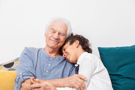 Happy boy cuddles his grandfather on a sofa. Concept of tenderness, family and joy.