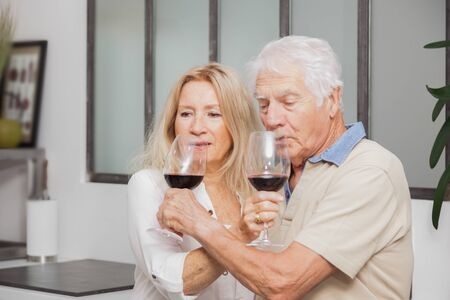 Happy senior couple relax talking and drinking red wine glasses together in the kitchen at home.
