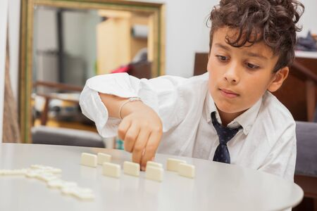 Boy playing game Dominoes.