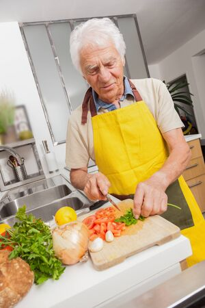 Happy senior man cooking with healthy food in a kitchen at home. Man with yellow tablier cutting vegetables. Banque d'images