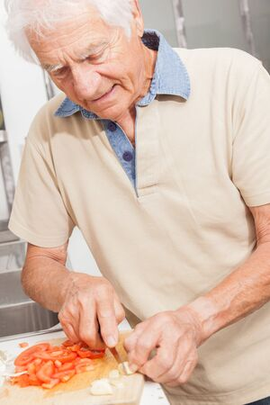 Happy senior man cooking with healthy food in a kitchen at home. White hair man cutting vegetables.