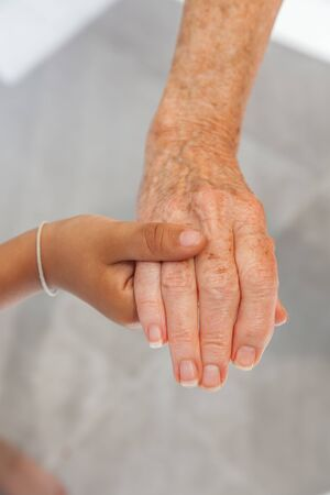 Young boy holding senior woman hands, close-up. Tender gesture between two generations.  Foto de archivo