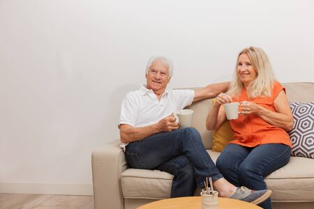 Happy senior couple drinking a tea, sitting on sofa in living.