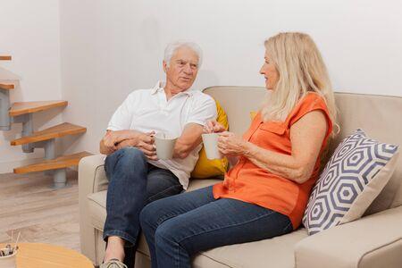 Happy senior couple drinking a tea, sitting on sofa in living.