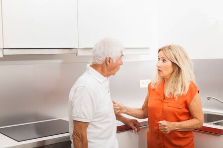 Senior couple chatting in a kitchen.