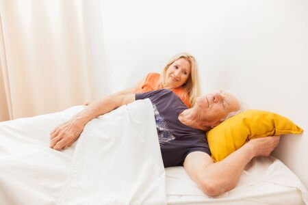 Senior couple in bed. Man sleeping et dreaming. Woman is awake in the bedroom. Banque d'images