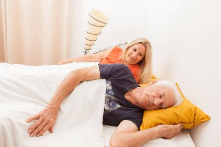 Senior couple in bed. Man sleeping et dreaming. Woman is awake in the bedroom. Imagens