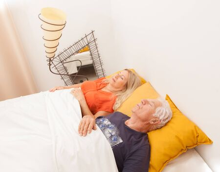 Senior couple sleeping and dreaming in bed in a bedroom.