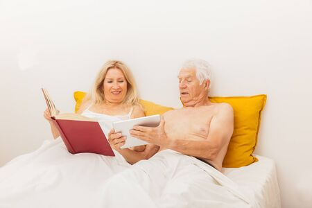 Senior couple reading and looking at a tablet in bed in a bedroom. Banque d'images