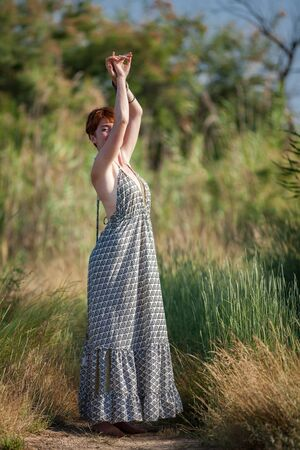 FREEDOM, WOMAN STANDING ARMS IN THE AIR OUTSIDE