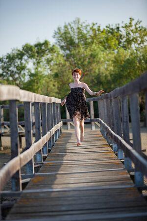 FREEDOM, HAPPY WOMAN RUNNING ON A GATEWAY