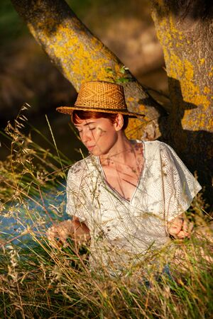 WELLNESS, RELAXATION, WOMAN WITH A STRAW HAT IN THE GRASS IN THE COUNTRYSIDE Stock Photo