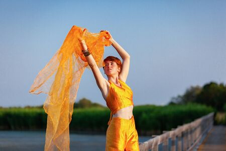 FREEDOM, MOVEMENTS, WOMAN ON A GATEWAY WITH A ORANGE SCARF Stock Photo