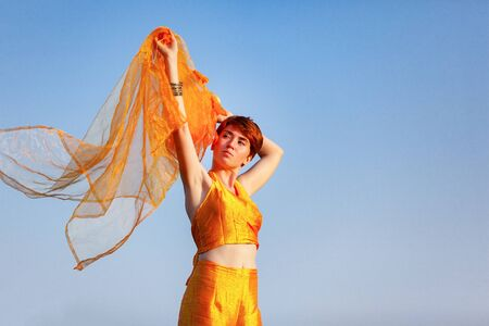 FREEDOM, MOVEMENTS, WOMAN ON A GATEWAY WITH A ORANGE SCARF