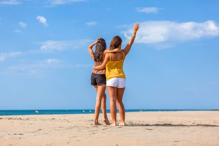 Complicity moment beetwen two girls best friends at the beach. Beautiful young women facing the sea. Stock Photo
