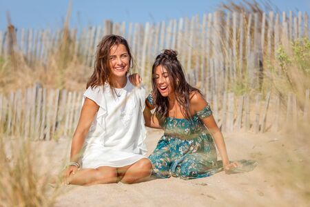 Complicity moment, relaxed women enjoying sun on vacations in dunes, enjoying beautiful nature, freedom and life at serene landscape beach. Concept of vacations, freedom, friendship, happiness, joy and well being.