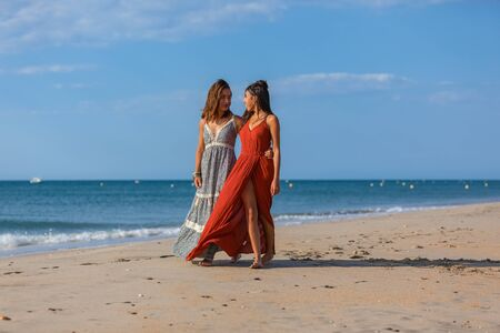 Complicity of two girls on the beach. Friends walking along the beach, laughing, having fun, lifestyle.
