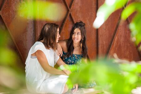 Complicity of two friends girls sitting cross-legged on the terrace of a country house. Happiness Lifestyle Friendship Concept.