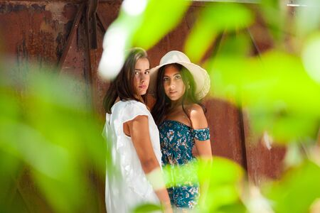 Complicity of two friends girls on the garden of a country house. Happiness Lifestyle Friendship Concept.